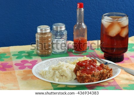 Meatloaf dinner on colorful place mat with hot sauce and salt and pepper shakers in background and served with a glass of ice tea.