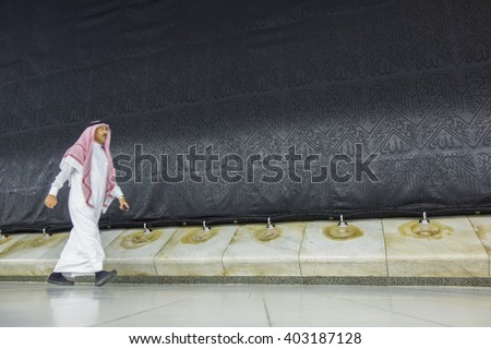 MECCA, S.ARABIA-DECEMBER 21, 2014: Motion blur of an unidentified Arab walks around the Kaabah in Makkah, Kingdom of SA. Muslims around the world face the Kaaba during prayer time. - stock photo