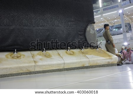 MECCA,S.ARABIA-DECEMBER 21, 2104:Police mosque guards one of the corners of Kaabah in Makkah, Kingdom of SA.Muslims around the world face the Kaaba during prayer time. - stock photo
