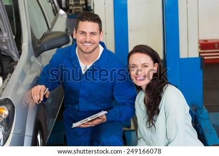 Mechanic and customer smiling at camera at the repair garage - stock photo