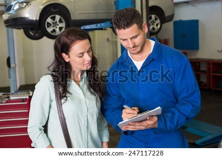Mechanic and customer talking together at the repair garage - stock photo