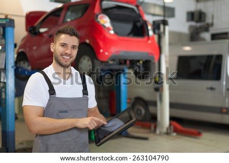 Mechanic at the car service. Smiling man in workshop posing with a digital tablet. - stock photo