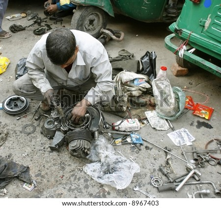 mechanic at workshop in delhi, india - stock photo