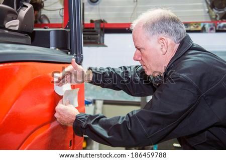 Mechanic Tightens Wheel Nuts On Fork Stock Photo - Forklift mechanic