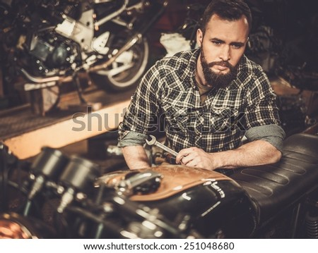 Mechanic building vintage style cafe-racer motorcycle  in custom garage - stock photo