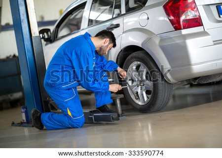 Mechanic change tyre on car - stock photo