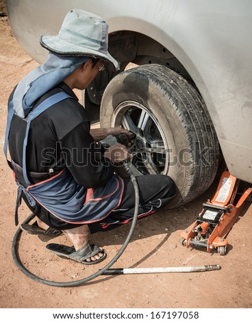 Mechanic changing a car tire - stock photo