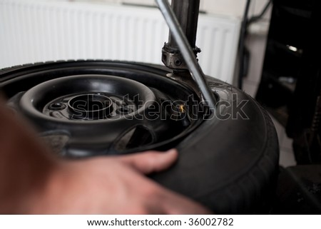 Mechanic changing a car tire closeup
