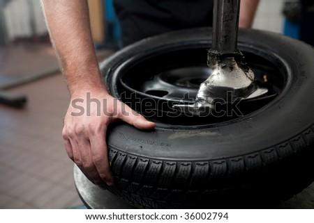 Mechanic changing a car tire closeup - stock photo