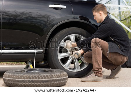 Mechanic changing a wheel during a roadside assistance call out to assist a driver in an emergency following a puncture