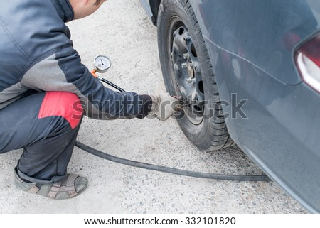 mechanic changing a wheel of a modern car (color toned image) - stock photo