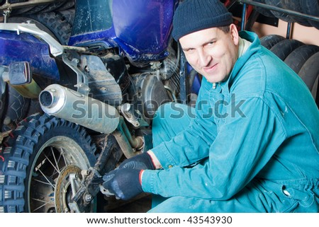 mechanic changing car tire in garage - stock photo