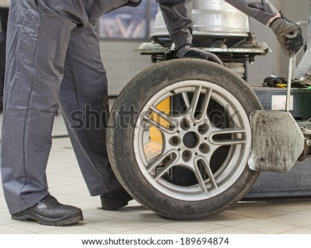 Mechanic changing car tire with bead breaker tool.