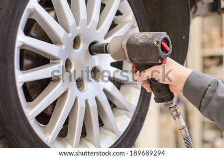 Mechanic changing car wheel at service. - stock photo