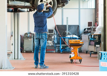 Mechanic changing car wheel in auto repair shop - stock photo