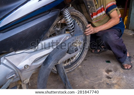 mechanic changing motorcycle tire in garage. - stock photo