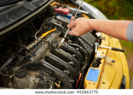Mechanic changing spark plugs on yellow car outdoor.