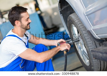 Mechanic changing wheel on car with impact wrench - stock photo