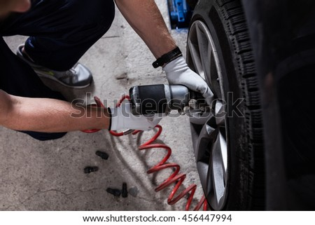 Mechanic changing wheel on car with pneumatic wrench.
