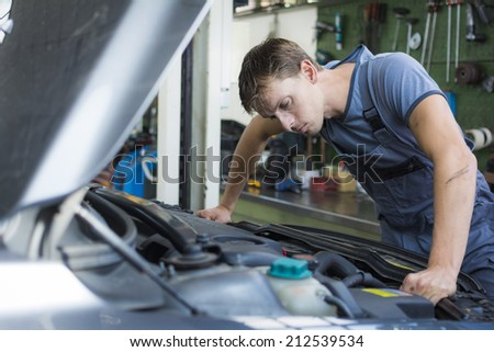 Mechanic checking a car in a garage - stock photo