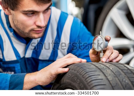 Mechanic, checking a measurement gauge to check the depth of a tread on a car tire for wear, to make sure it is still within regulations and safe to use. Focus on the hands and the gauge - stock photo