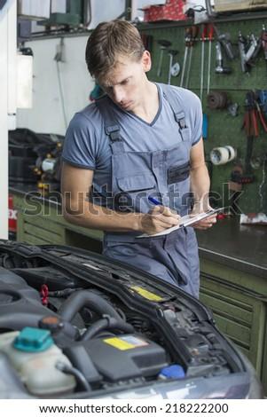 mechanic checking car at garage - stock photo