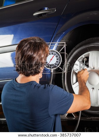 Mechanic Checking Gauge While Inflating Car Tire