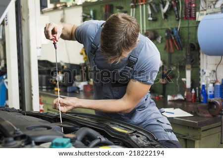 mechanic checking oil of a car - stock photo