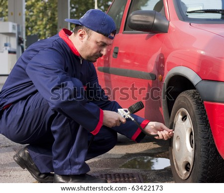 Mechanic Checking Tyre Pressure at Gas Station - stock photo