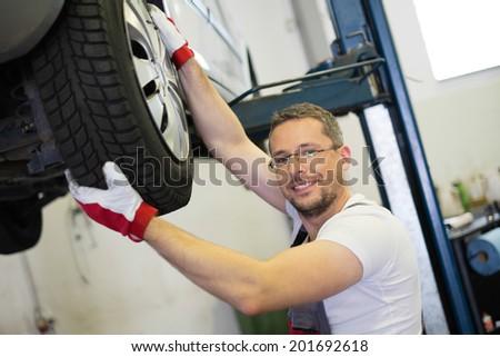 Mechanic checking wheel bearings in a car workshop - stock photo