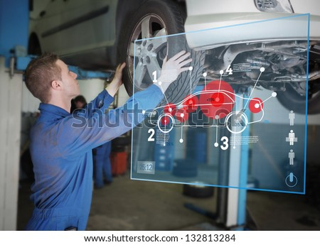 Mechanic checking wheel of a car helped by futuristic interface - stock photo