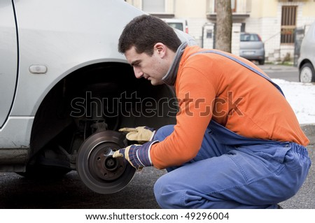 mechanic checking worn car brake