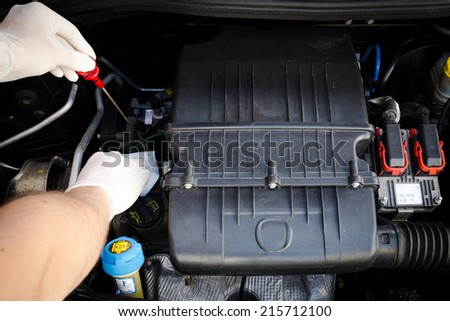 mechanic checks the oil level - stock photo