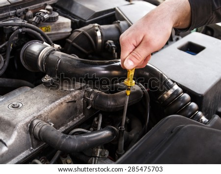 Mechanic checks the oil on a car being repaired