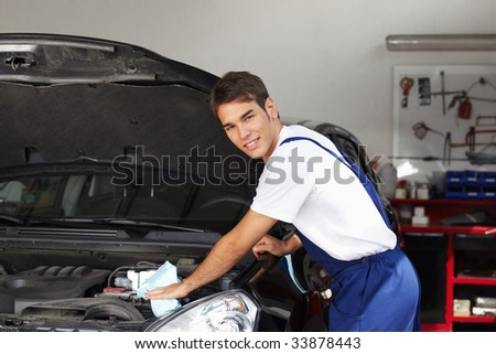 mechanic cleaning car engine and looking at camera - stock photo