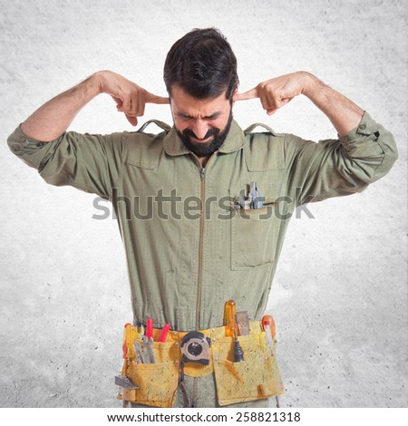 Mechanic covering his ears  - stock photo