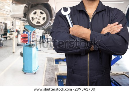 Mechanic cross arm holding wrench for maintaining car on lift at the repair shop - stock photo