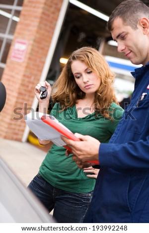 Mechanic: Customer And Service Tech Look At Bill - stock photo