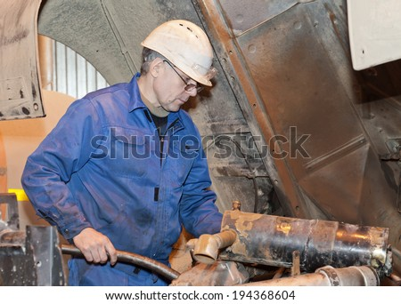 mechanic dressed in dirty overalls serves mechanisms - stock photo