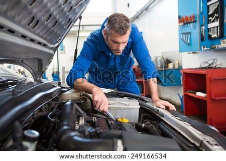Mechanic examining under hood of car at the repair garage - stock photo