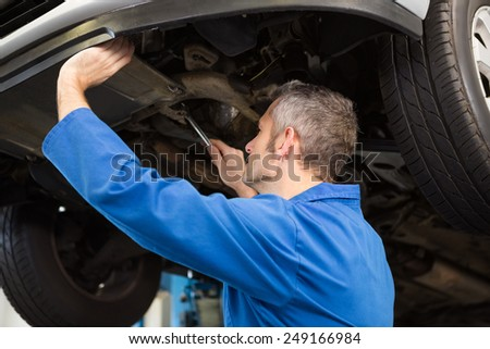 Mechanic examining under the car at the repair garage