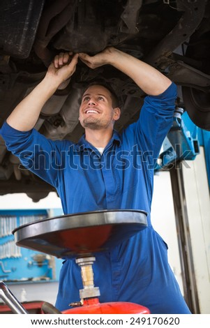 Mechanic examining under the car at the repair garage - stock photo