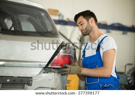 Mechanic fixes backlight on car