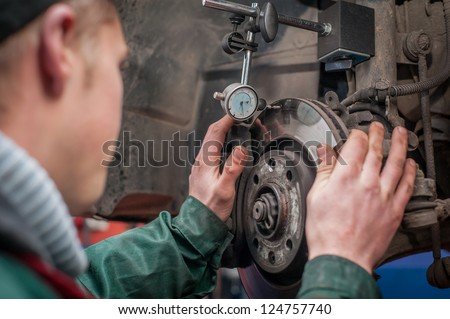 Mechanic fixing car disc breakes - stock photo