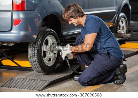 Mechanic Fixing Car Tire At Repair Shop - stock photo