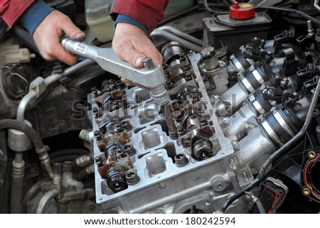 Mechanic fixing cylinder head with camshaft of car engine with socket wrench