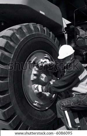 mechanic fixing giant tire on a forklift truck - stock photo