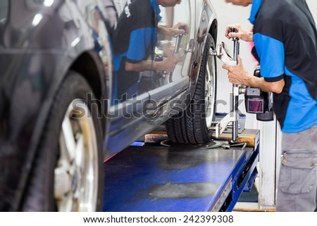 Mechanic fixing the wheel alignment device onto a car wheel. Focus is on the car wheel and wheel alignment device. - stock photo