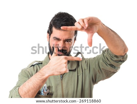 mechanic focusing with his fingers  - stock photo