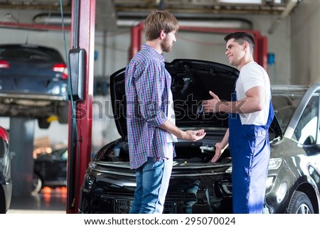 Mechanic giving client keys to his repaired car - stock photo